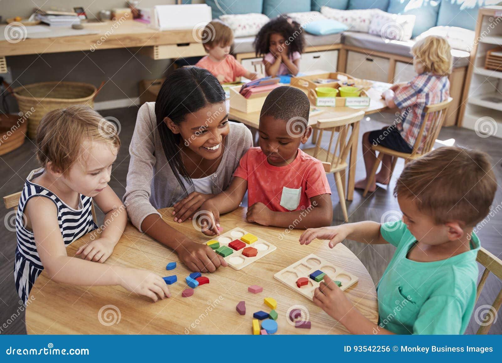 Nauczyciel I ucznie Używa Drewnianych kształty W Montessori szkole