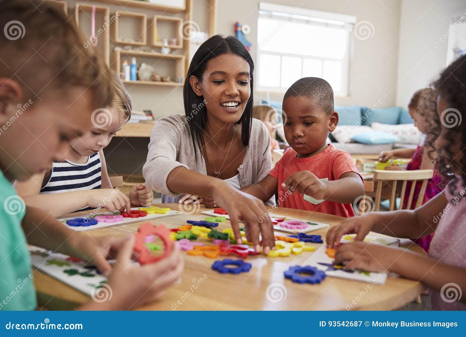 Nauczyciel I ucznie Używa kwiatów kształty W Montessori szkole