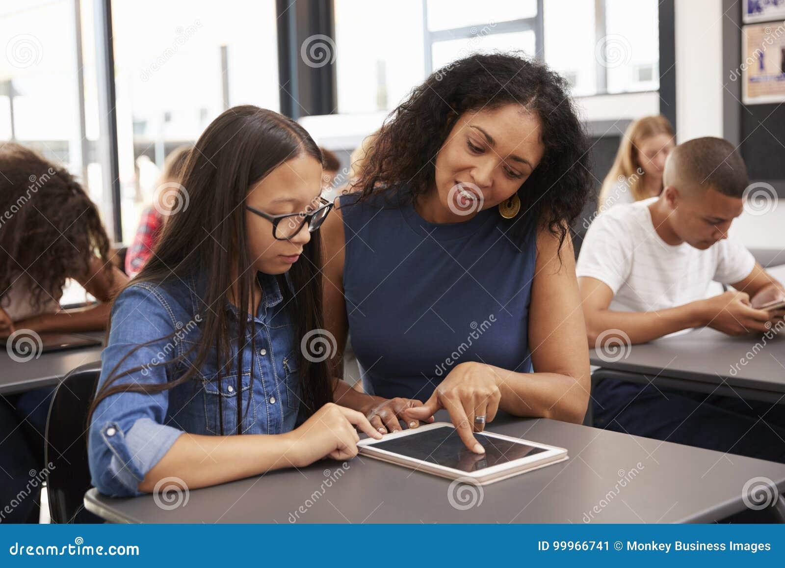 Nauczyciel pomaga nastoletniej uczennicy z pastylka komputerem