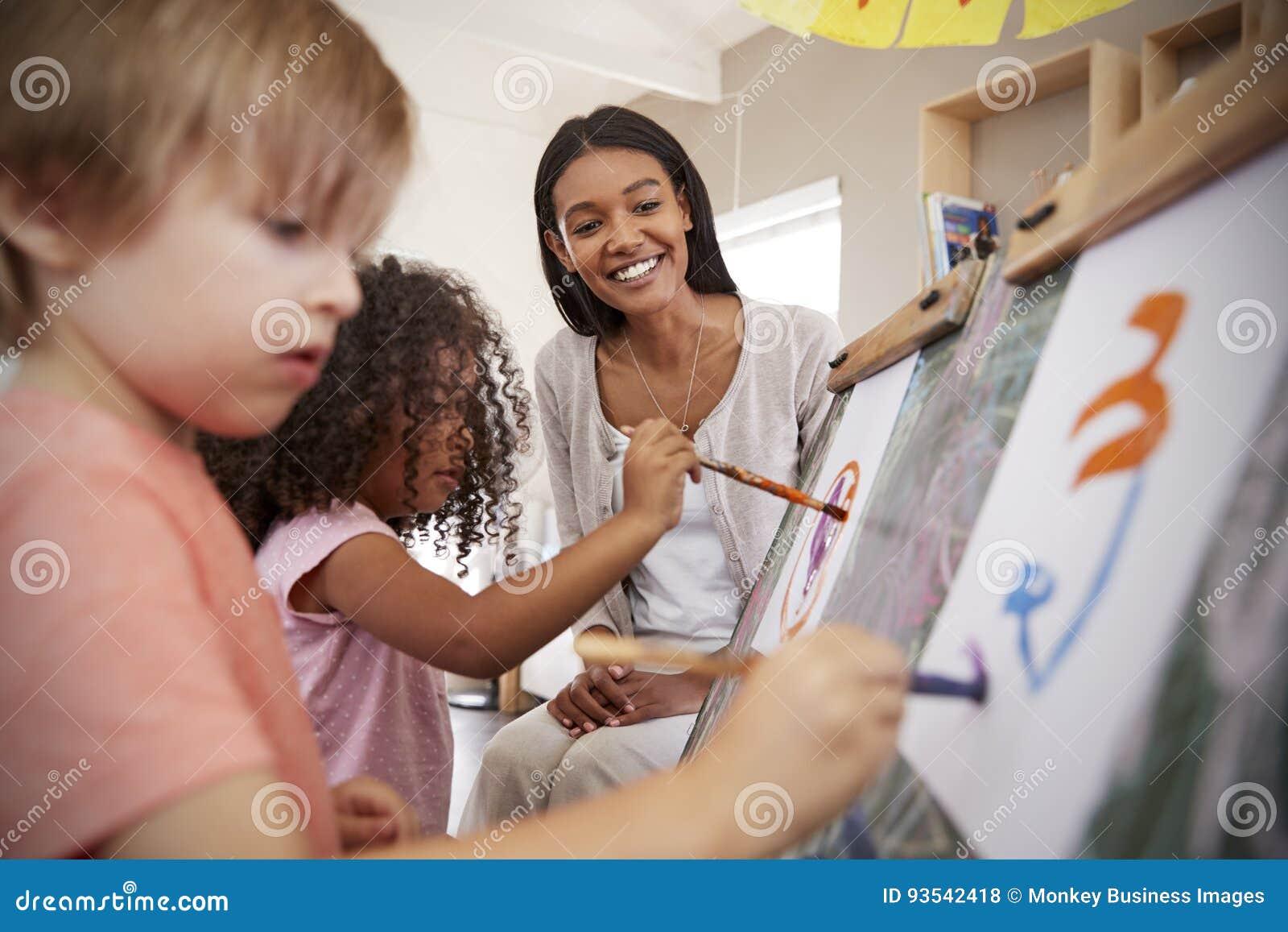 Nauczyciel Przy Montessori szkoły Pomaga dziećmi w sztuki klasie