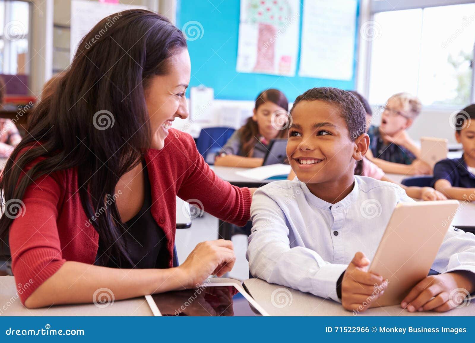 Nauczyciel szkoły podstawowej pomaga chłopiec używa pastylka komputer