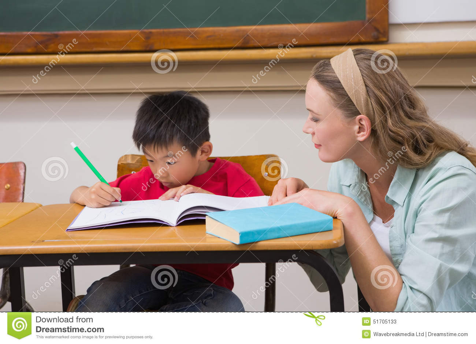 Nauczyciela pomaga uczeń w sala lekcyjnej