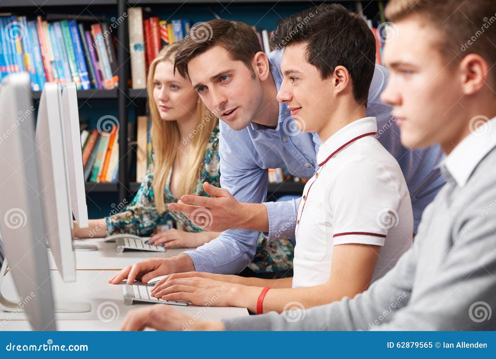 Nauczycieli Pomaga ucznie Pracuje Przy komputerami