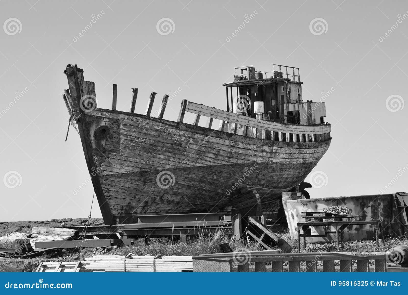 Naufrágio oxidado de madeira e do metal na doca seca islandêsa na cidade de Akranes como um símbolo da corrosão e da deterioração