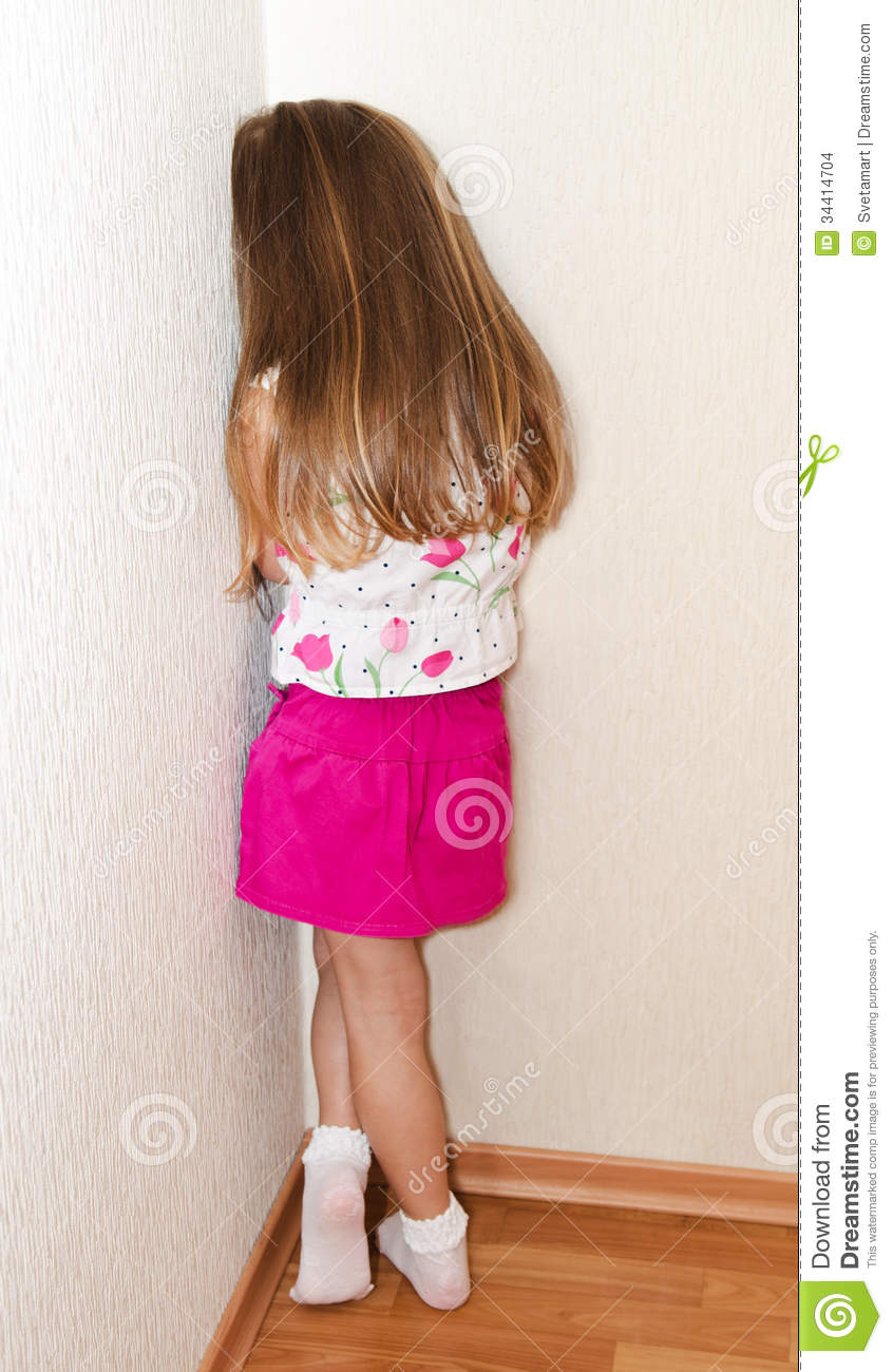 Standing In The Corner : Naughty little girl is standing in the corner stock images