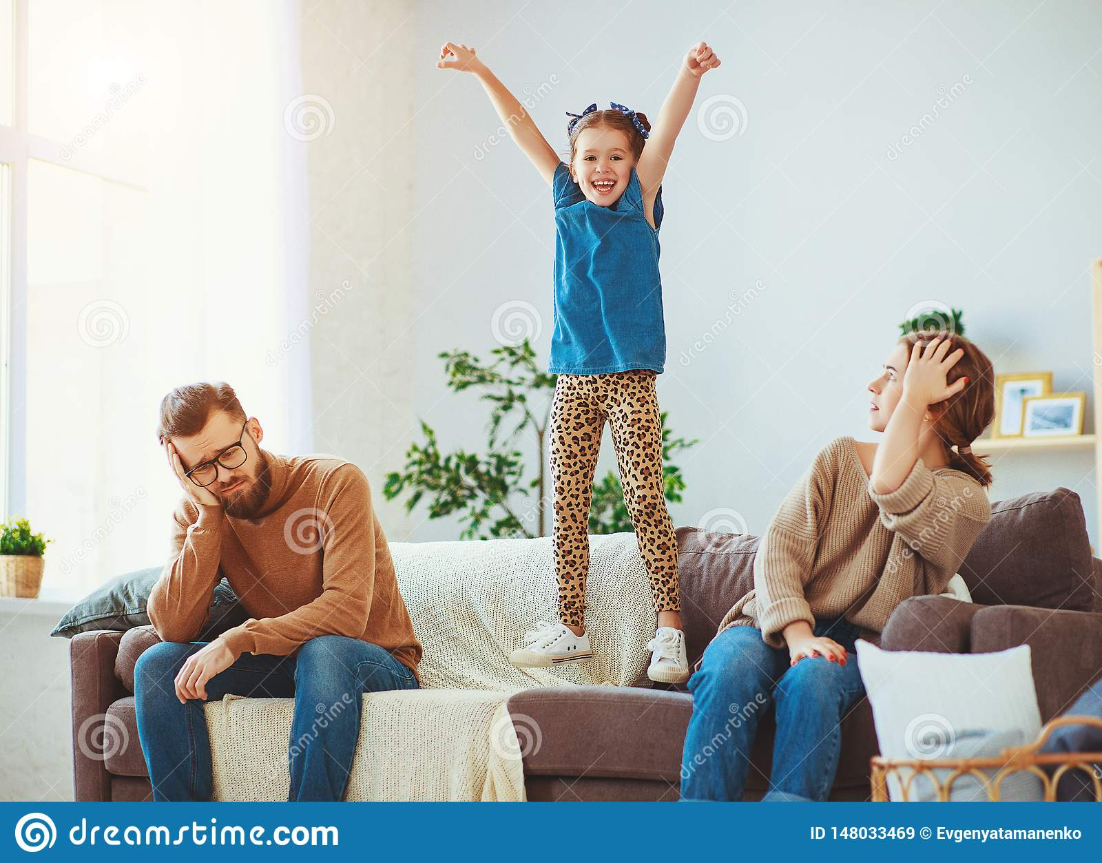 Naughty, mischievous, child girl jumping, laughing and having fun, parents stressed with  headache