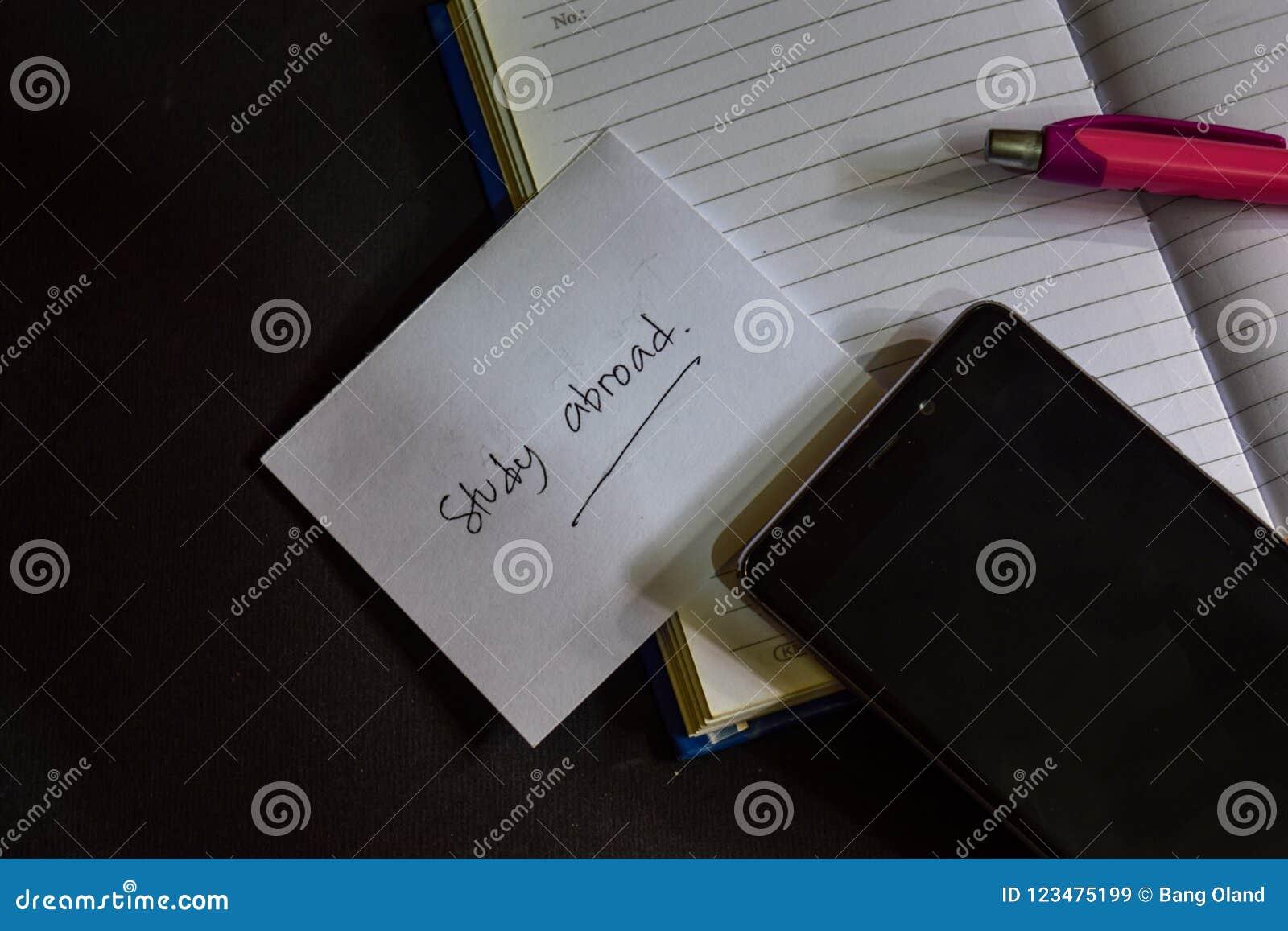 Nauki za granicą słowo pisać na papierze studiuje za granicą tekst na workbook, Czarny tła pojęcie