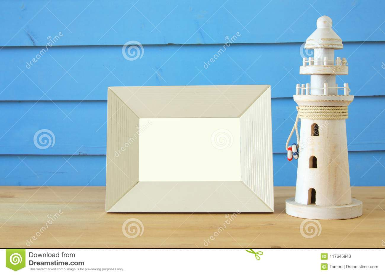 Nautical concept with empty photo frame and lighthouse over wooden table. For photography montage.