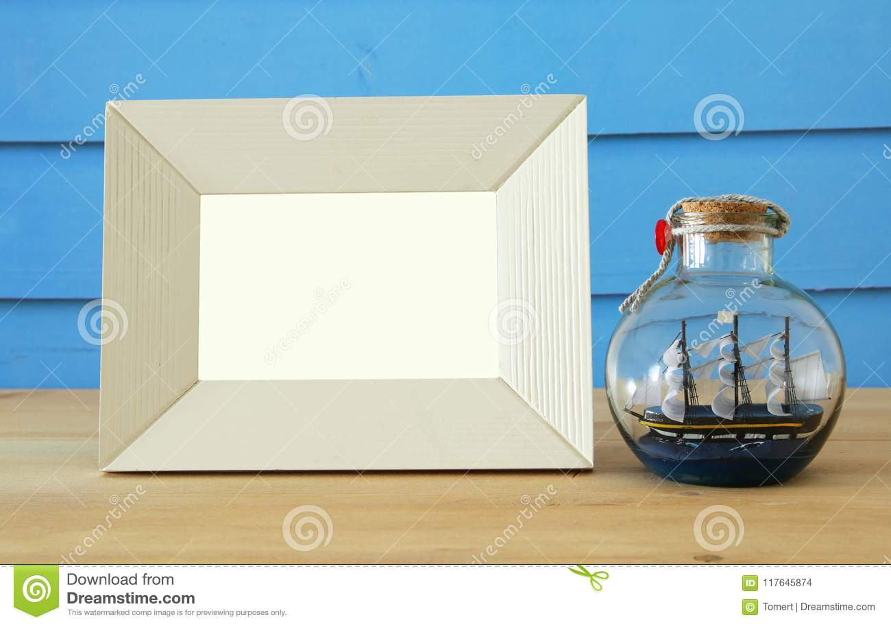 Nautical concept with empty photo frame and sail boat in the bottle over wooden table. For photography montage.