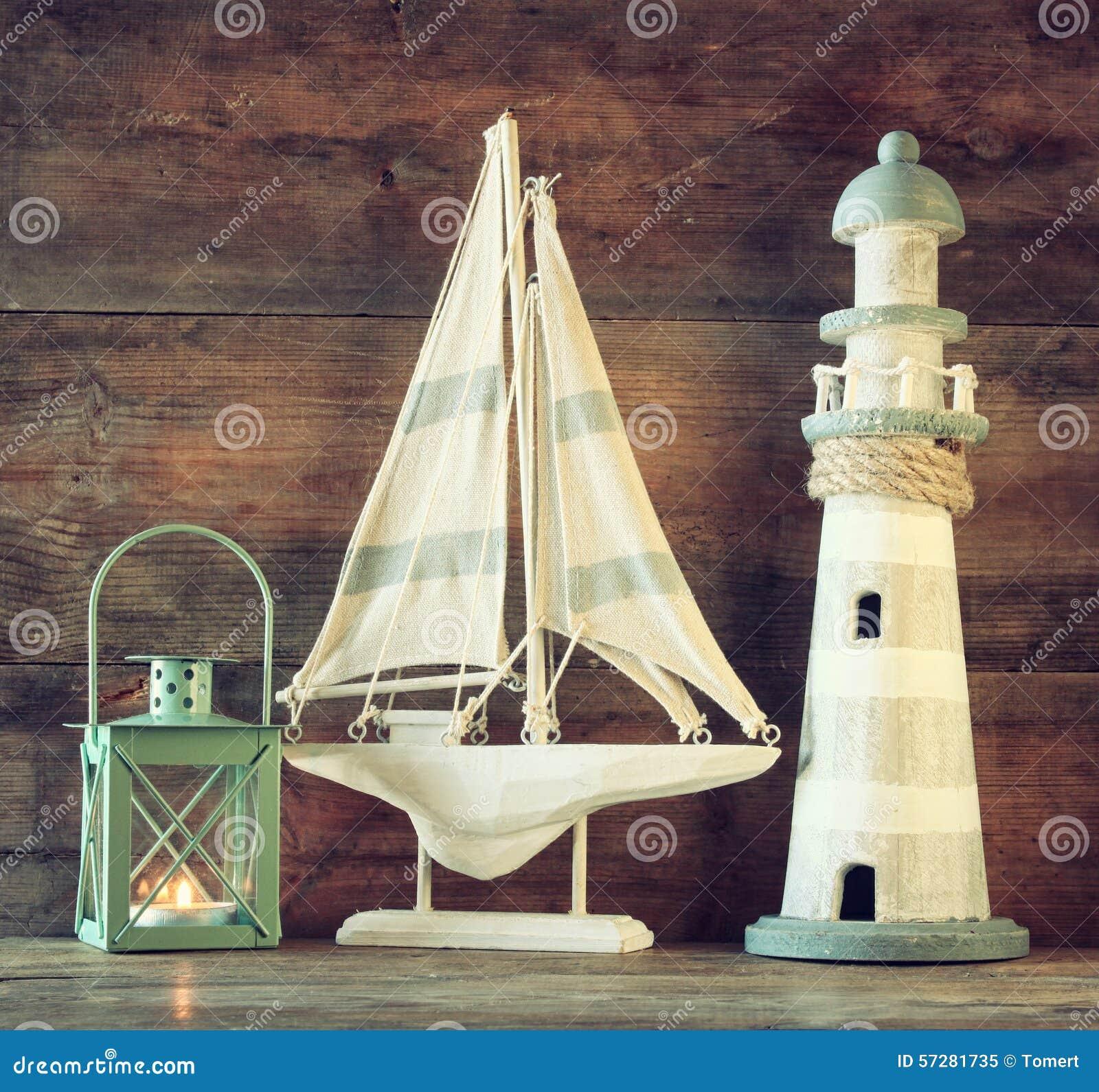 Nautiskt livsstilaftonbegrepp gammal tappningfyr, segelbåt och lykta på trätabellen tappning filtrerad bild