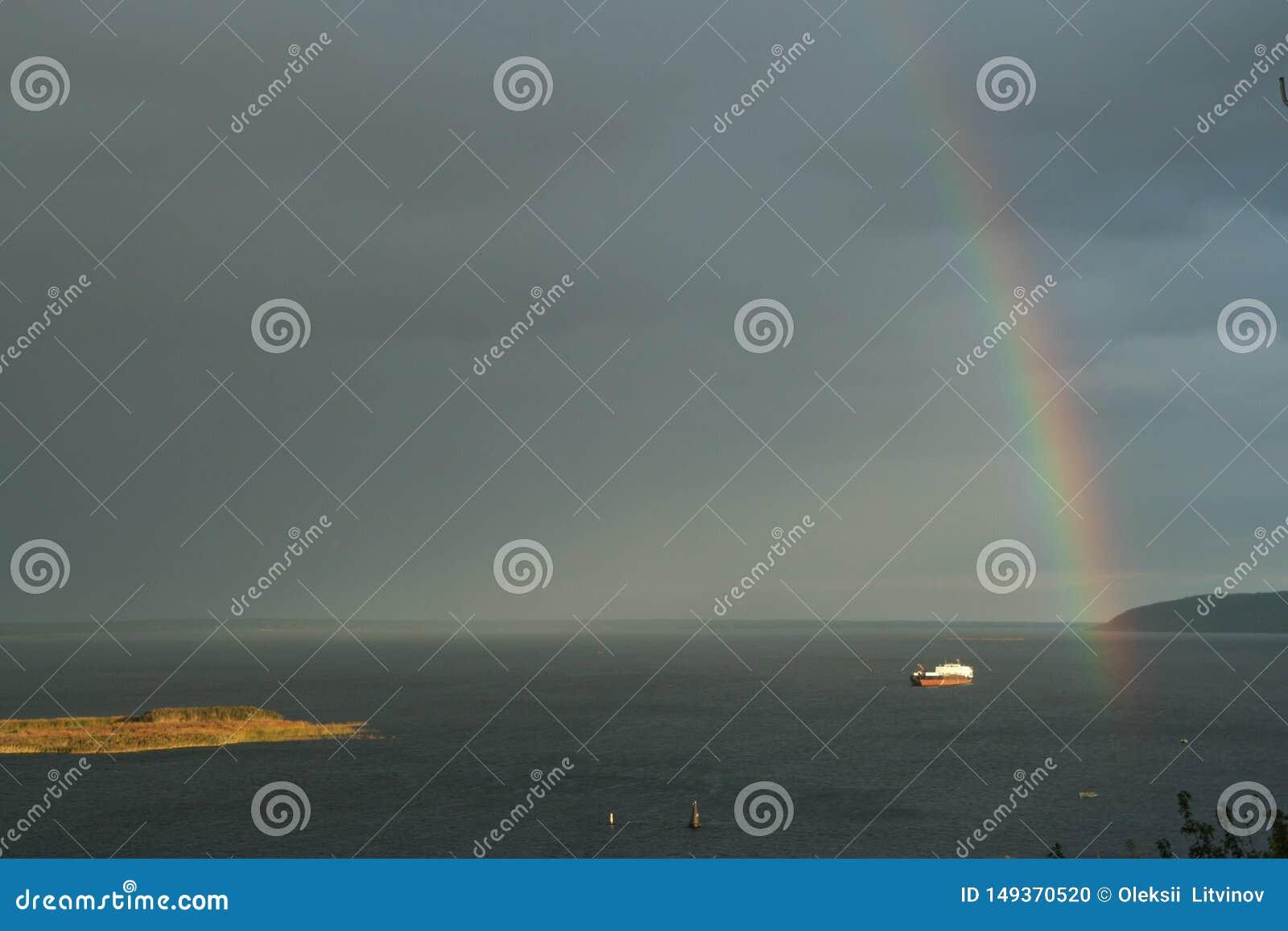 Nave sola en el r?o y un arco iris en el cielo