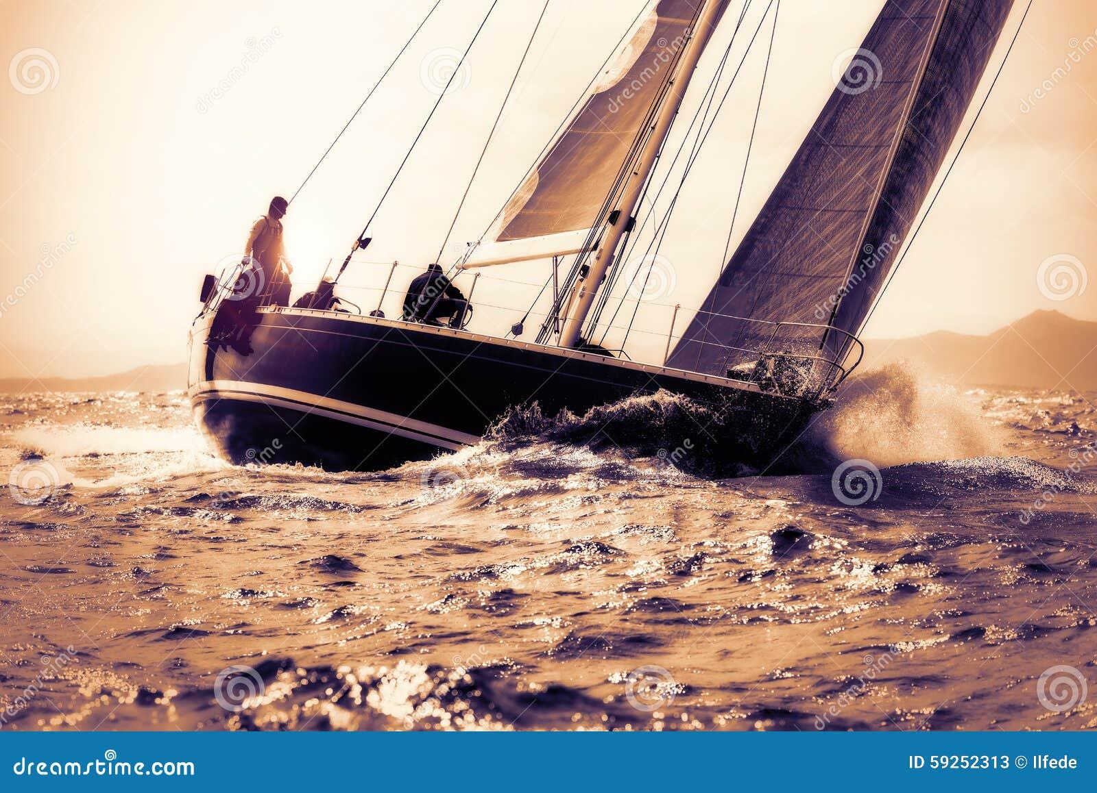 Navegación del barco de vela en puesta del sol