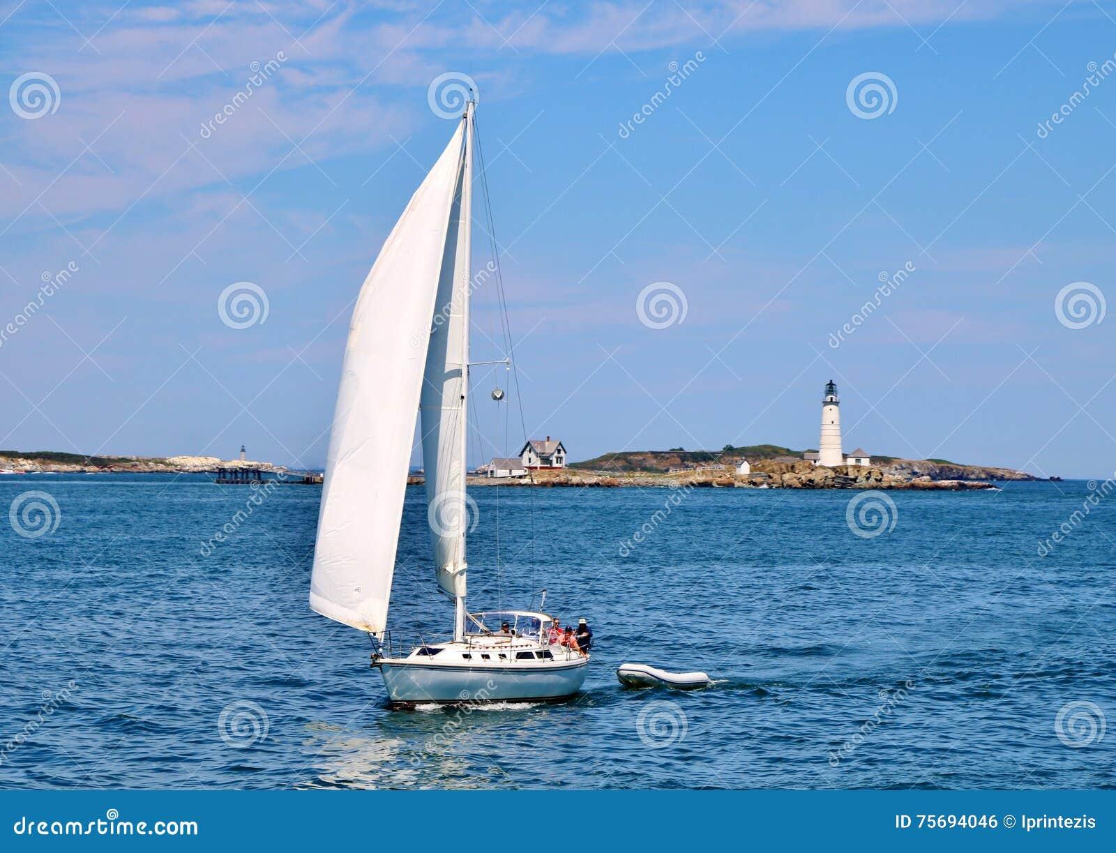 Navegación del yate delante del faro del puerto de Boston
