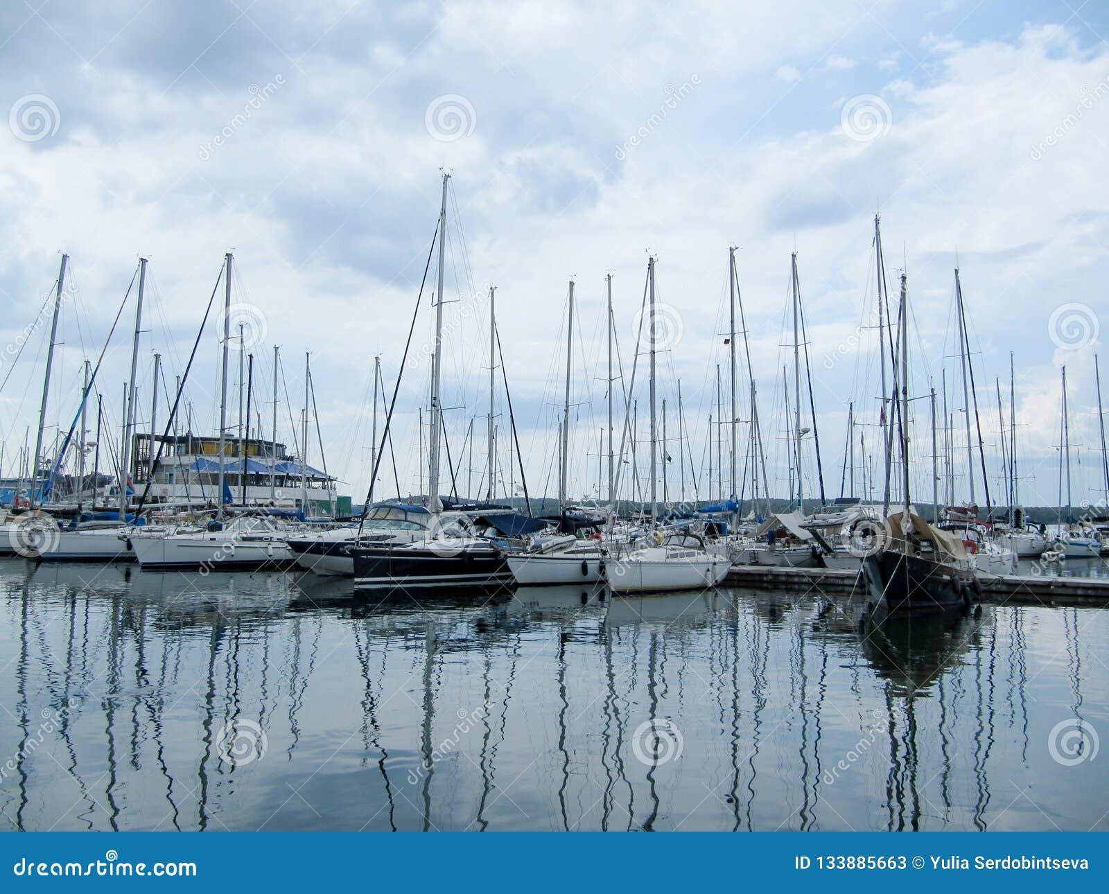 Navegando los yates se colocan con las velas bajadas en un pequeño puerto en un día nublado