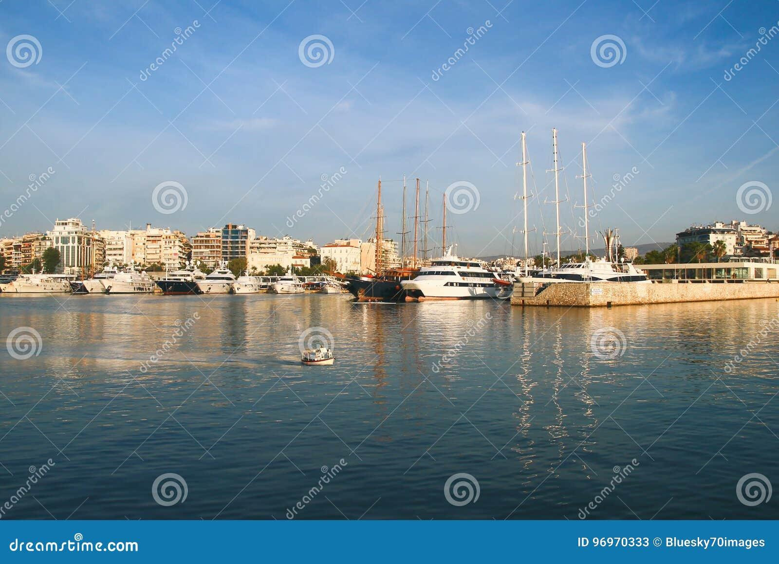 Navigação, barcos de motor e um barco de pesca pequeno que cruza águas calmas no porto do porto Zeas Pireas Greece