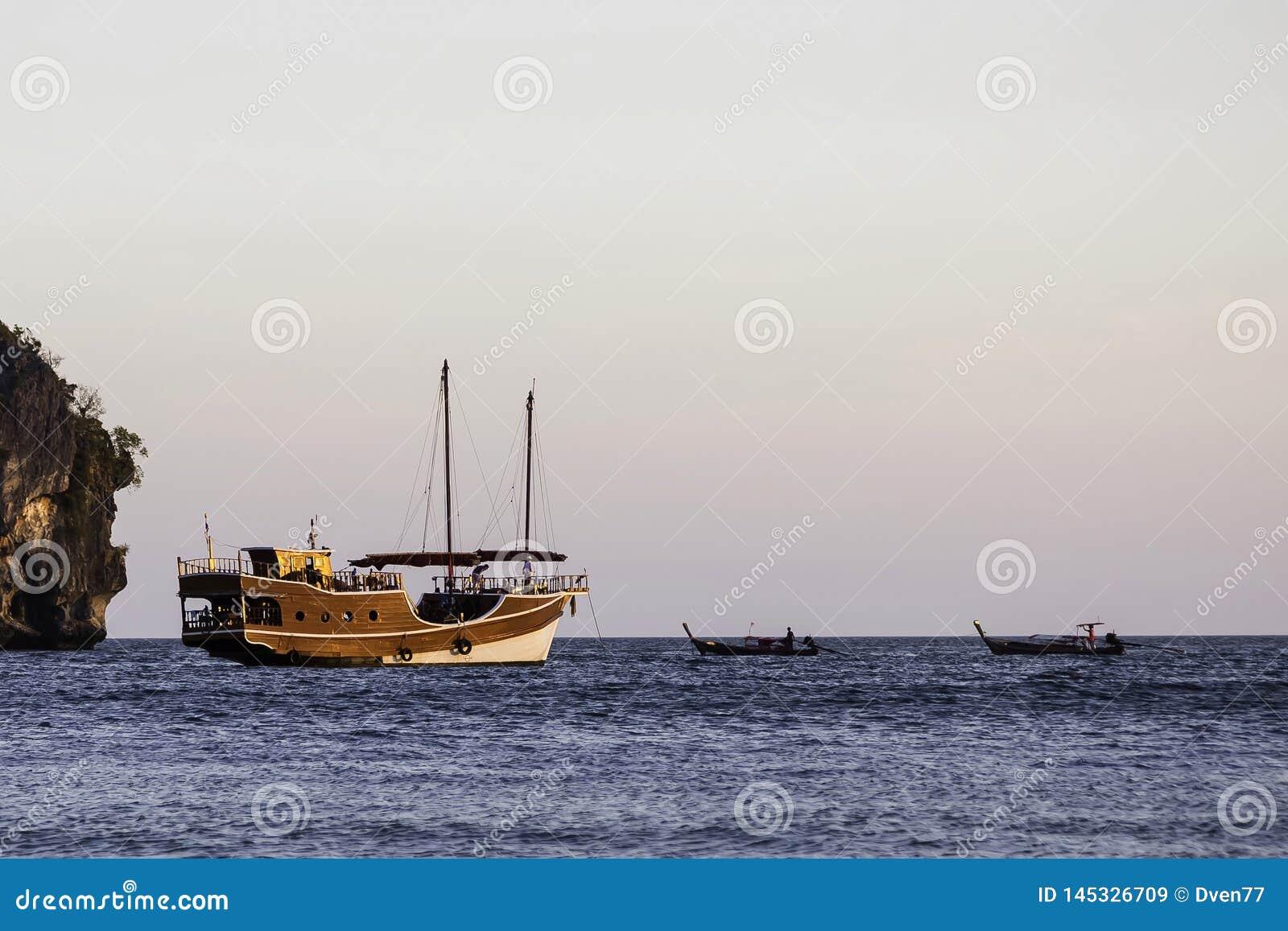 Navigation du bateau en bois dans les voiles de style ancien sur la mer Tout près il y a deux petits bateaux longs-courriers