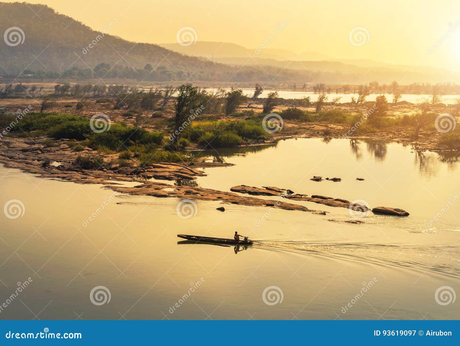 Navigation en bois de bateau de pêche dans le Mekong sur le lever de soleil à la frontière de la Thaïlande et du Laos