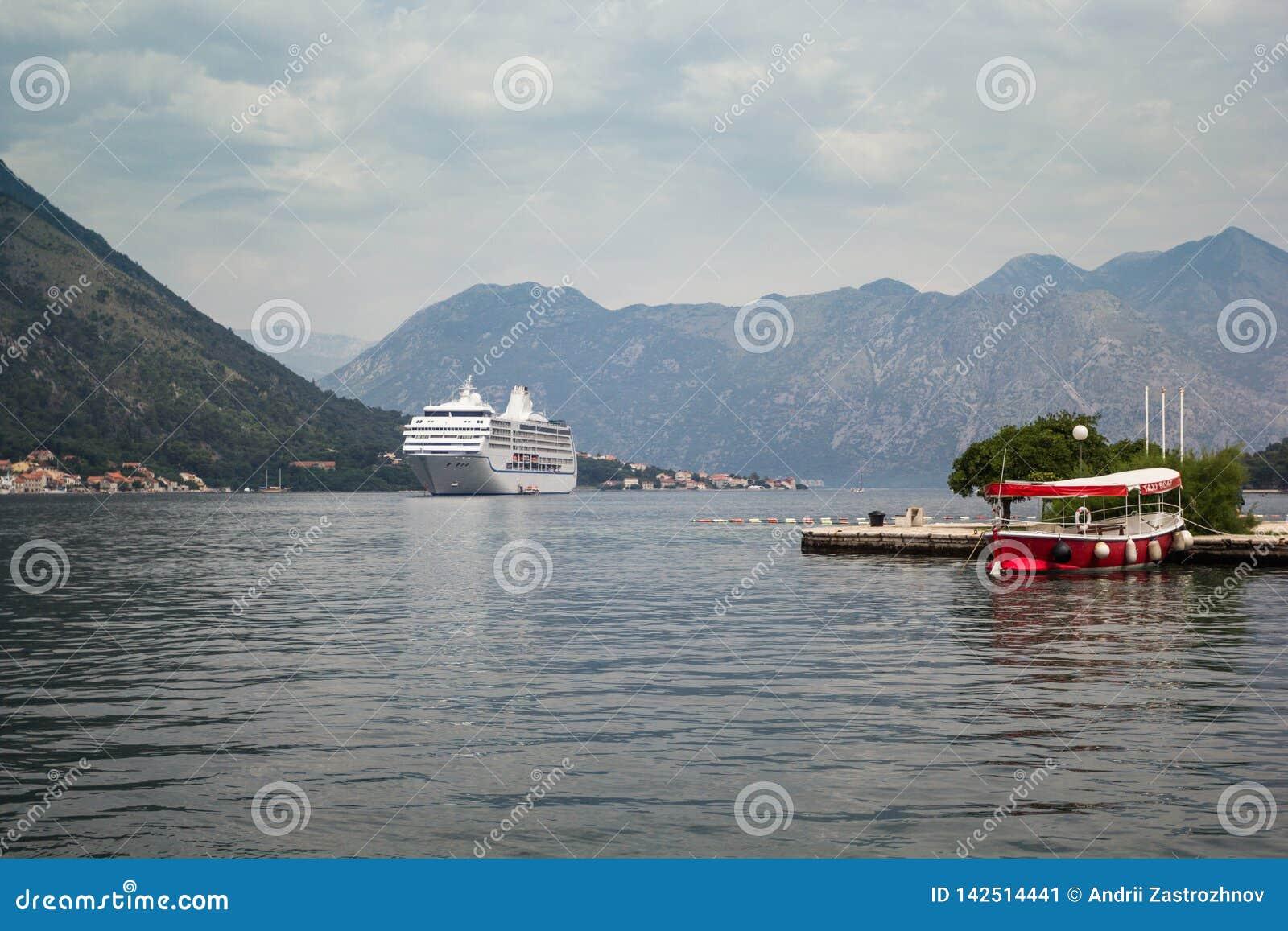 Navio de cruzeiros na baía entre as montanhas, o barco do táxi no cais no primeiro plano