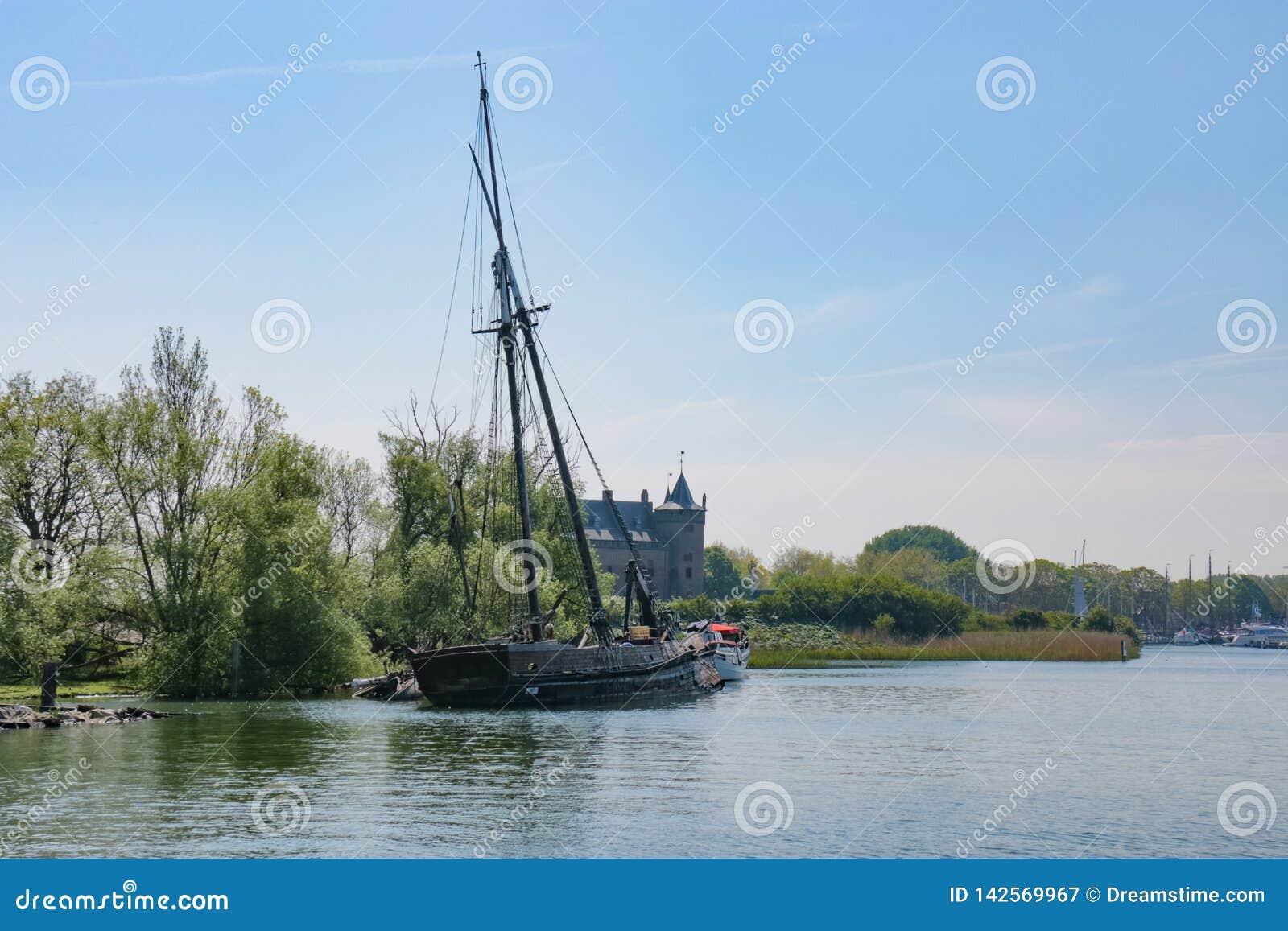 Navio de navigação destruído velho no lado do canal do rio