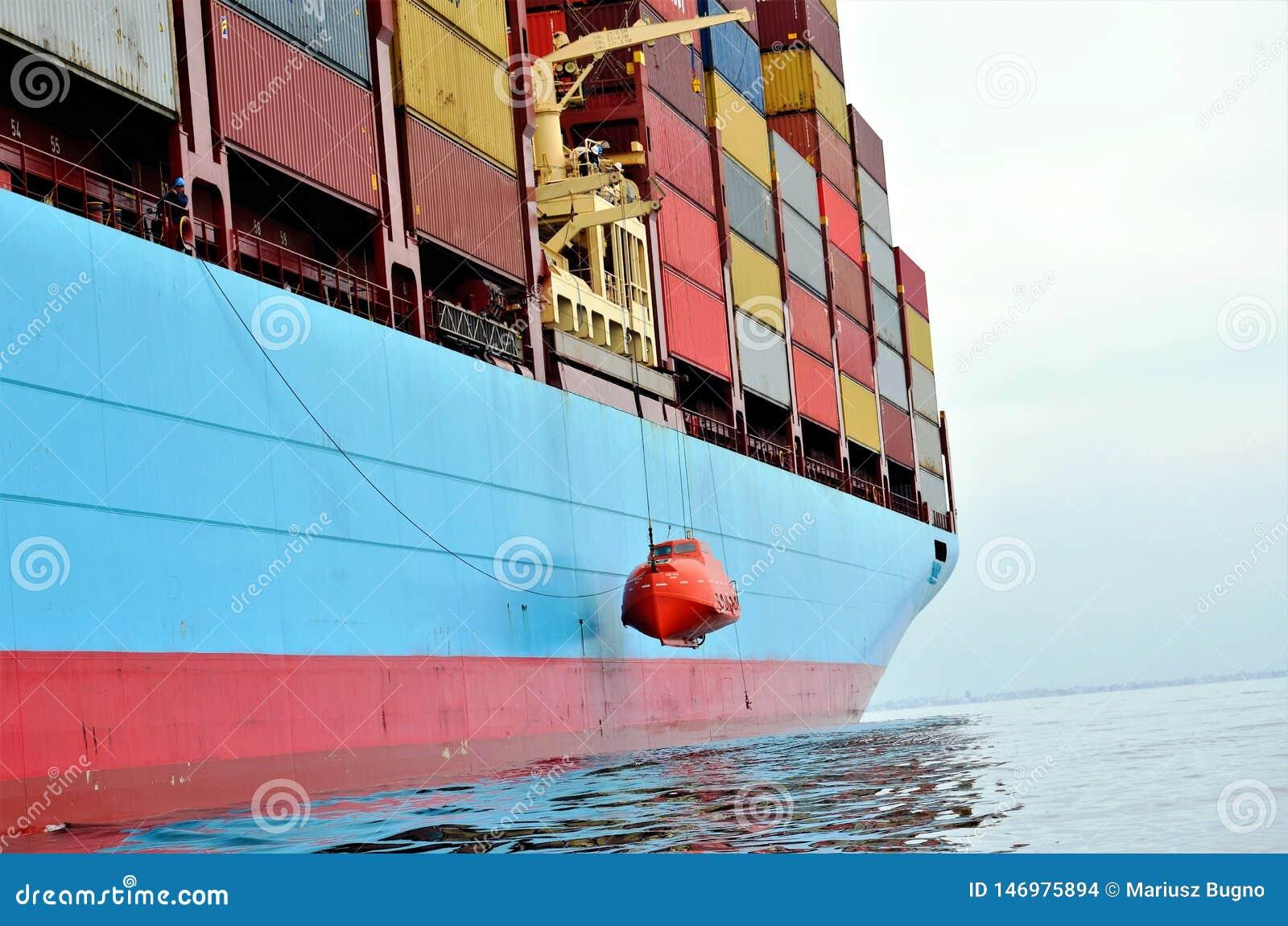 Navio de recipiente na âncora, esperando para entrar no porto