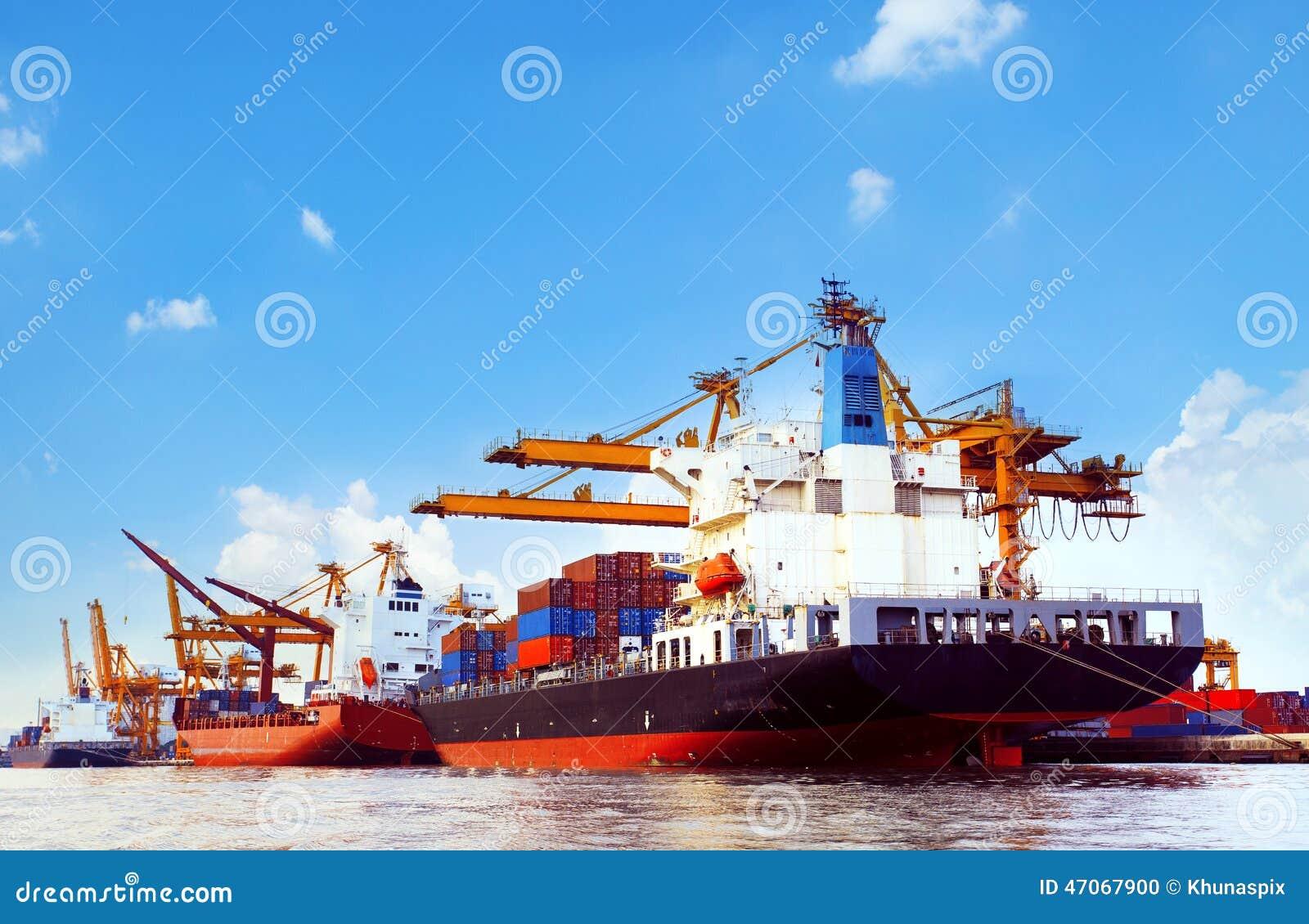 Navio de recipiente na doca da carga do porto com uso da ferramenta do guindaste dos cais para