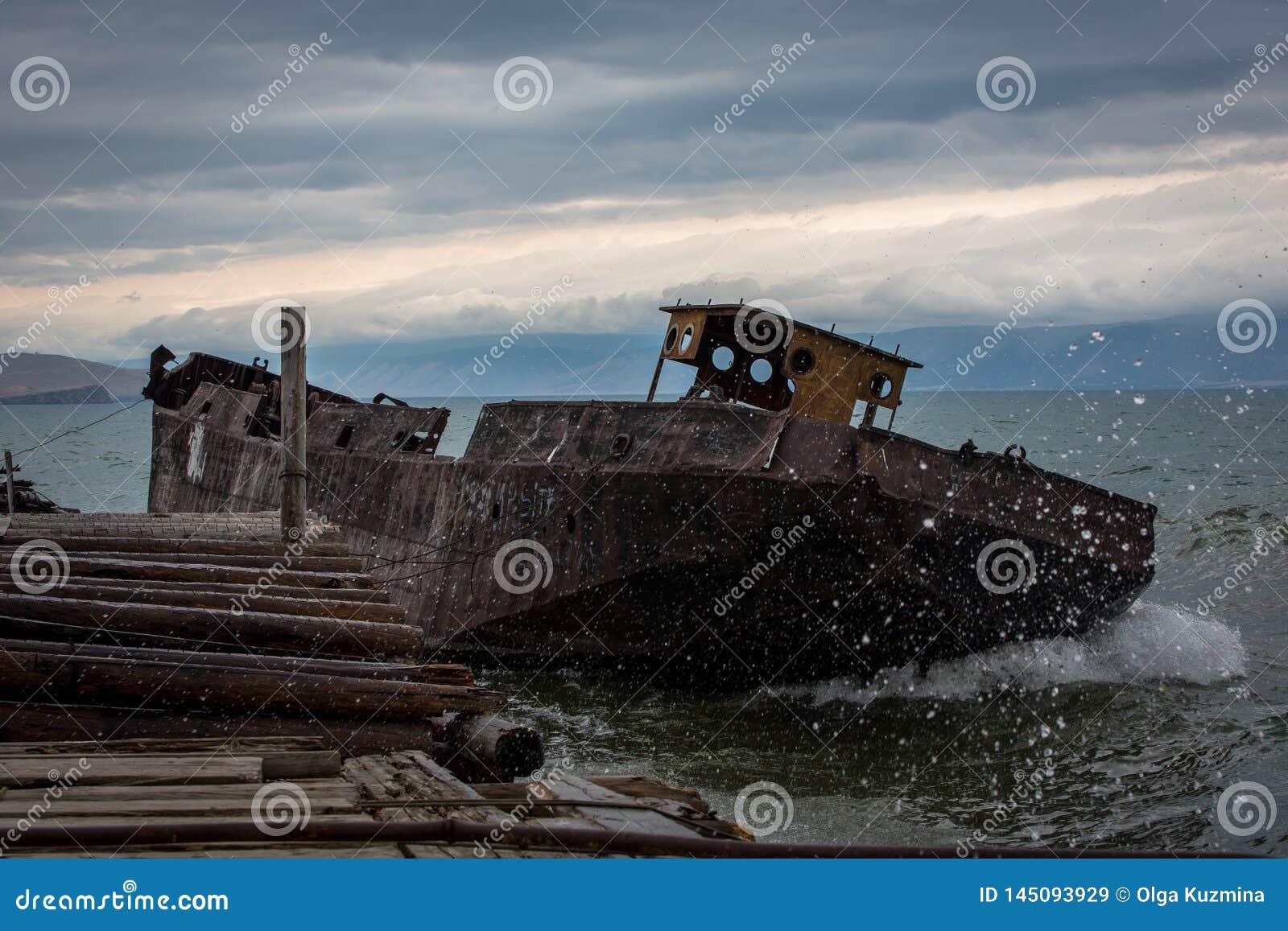 Navio velho, oxidado perto do cais As ondas grandes inundam a plataforma Noite nebulosa do ver