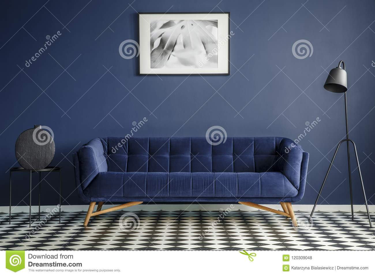 Navy blue room interior with comfortable plush couch in the midd