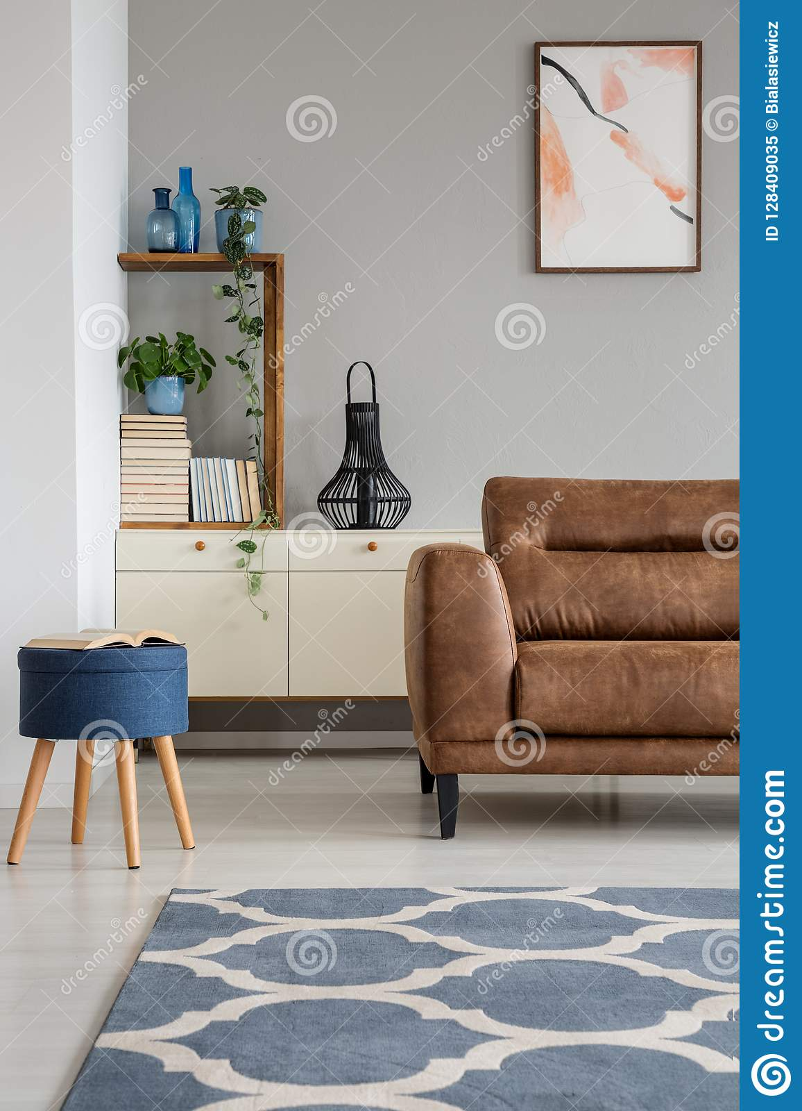Navy Blue Stool Next To Leather Sofa In Grey Living Room ...