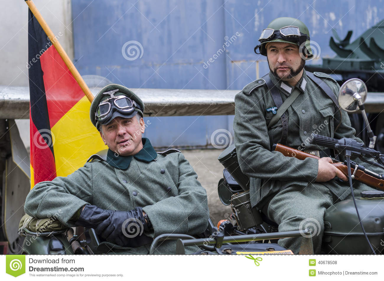 Nazi officer with bodyguard soldier stand on combat car with german