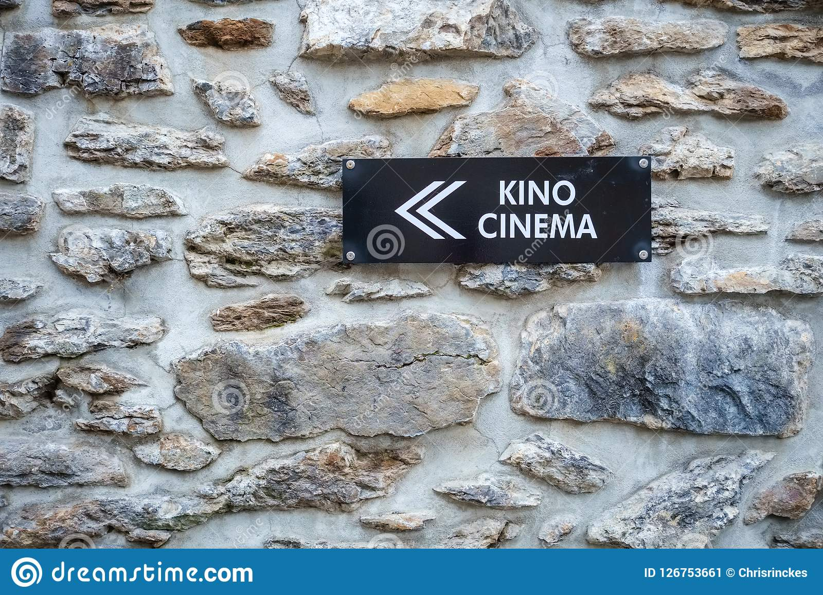 Cinema sign against a stone wall near Wengen. Near the city of Wengen Berner Oberland, Switzerland a cinema and bowling alley is located. The outside of the Stock Illustration