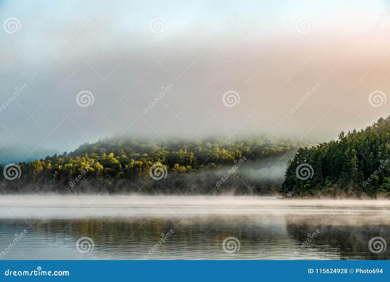Nebel des frühen Morgens hebt einen kleinen, reflektierenden See weg