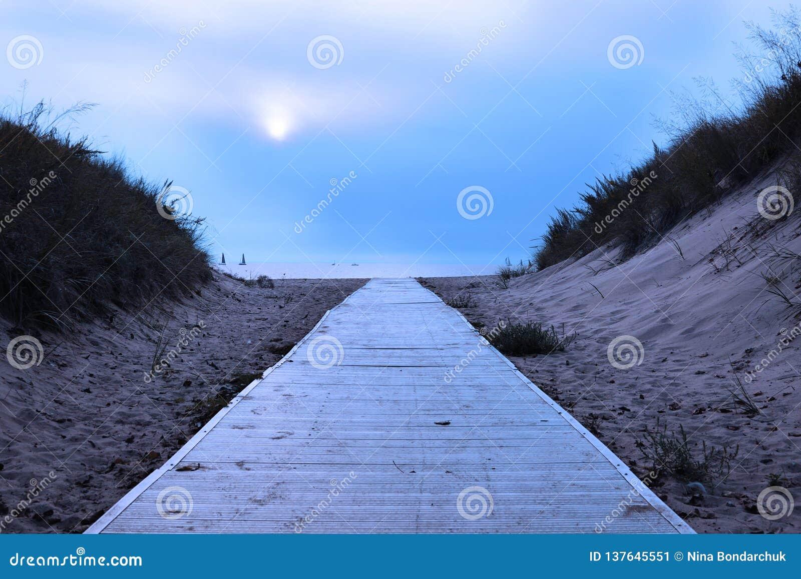 Nebelhaftes Meer und zwei Schattenbilder von Yachten Ein Fußgängerweg wird auf das Wasser verwiesen