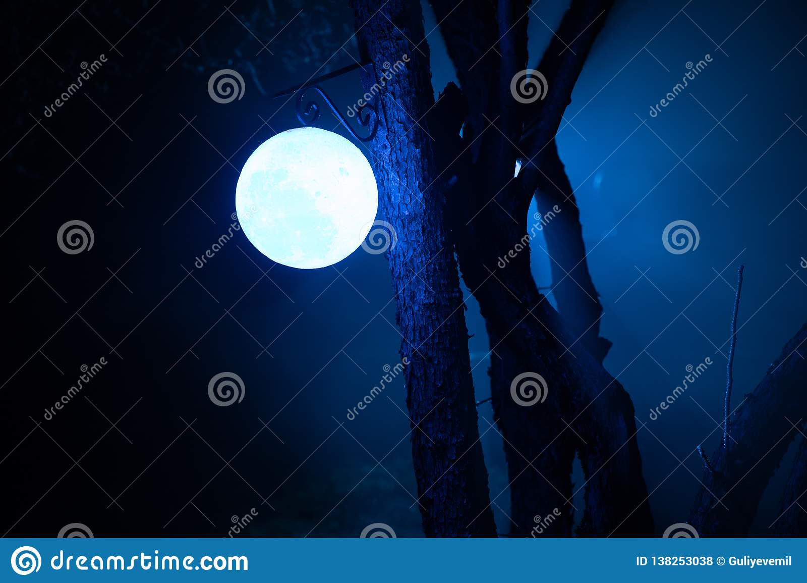 Nebeliges Nachtyard mit hellem Licht auf Hintergrund Laterne, die am Baum hängt