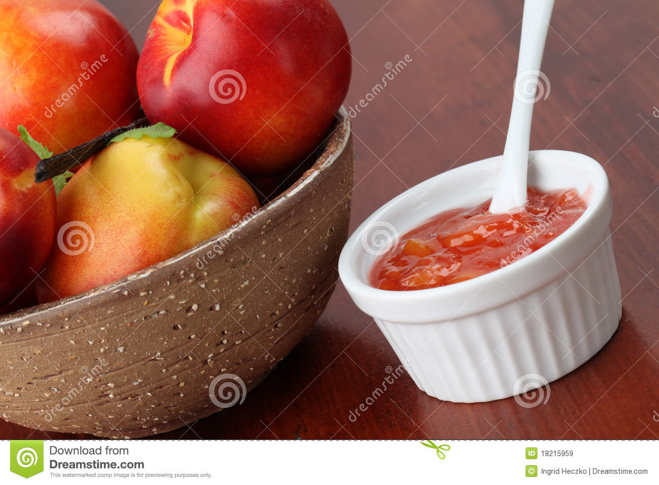 Nectarine jam in a white bowl and fresh nectarines.