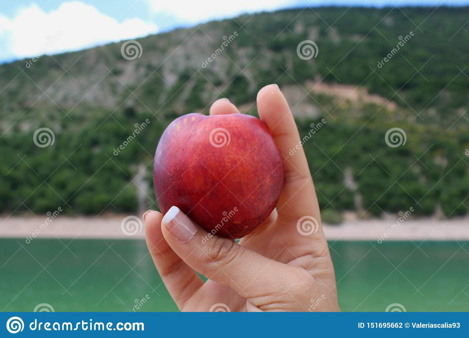 Peach in the hand by the lake