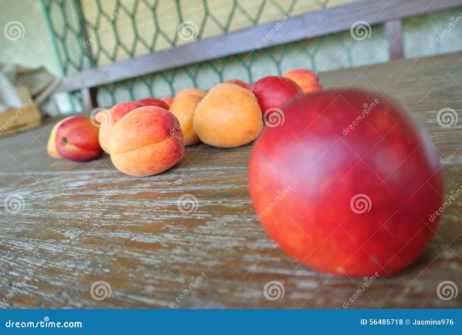 Nectarine rouge mûre et abricots oranges sur la table en bois rustique