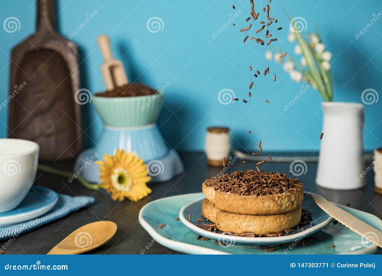 Nederlands ontbijt met beschuit en chocoladehagel hagelslag tegen blauwe achtergrond
