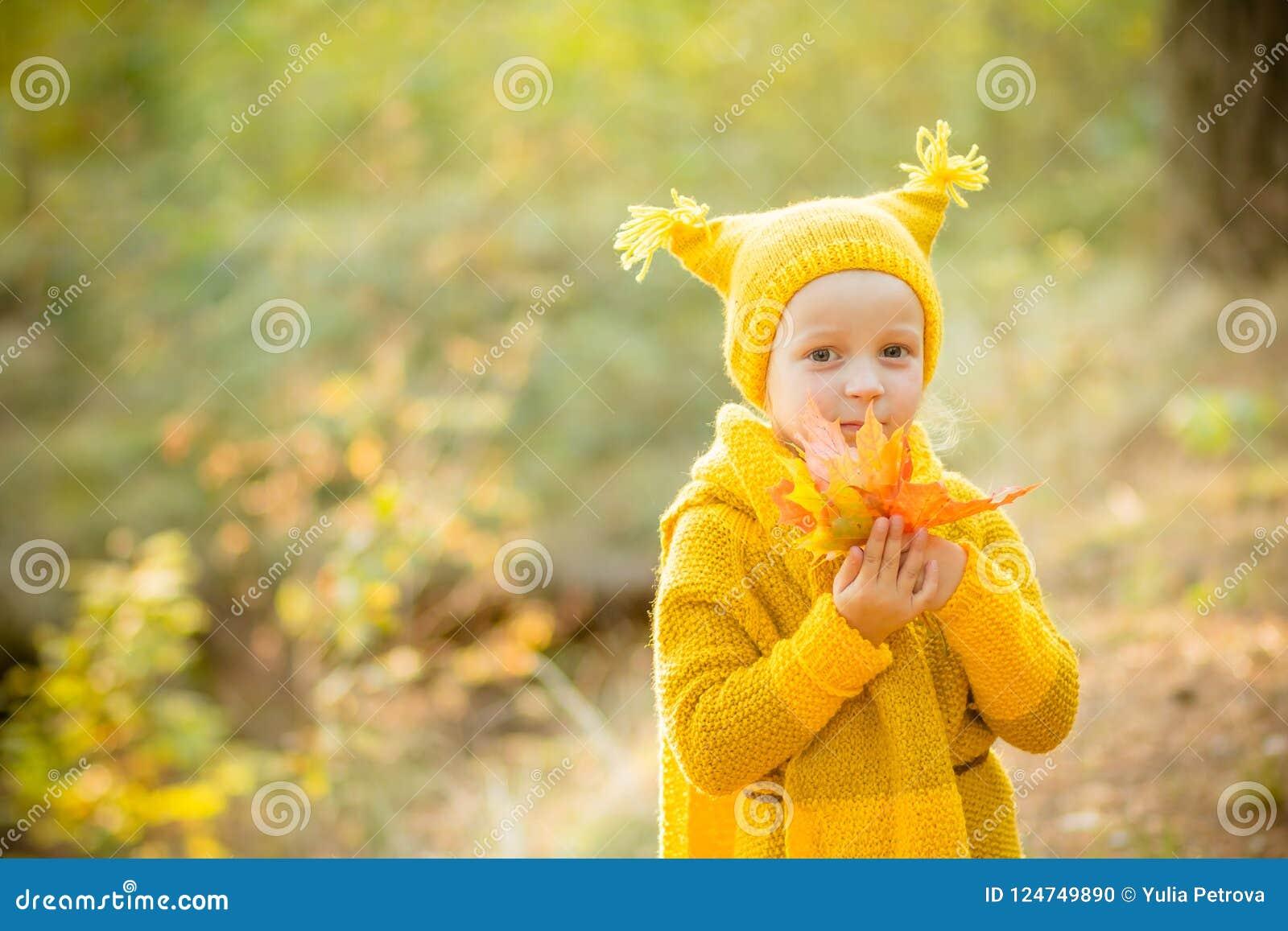 Nedgångsäsong och folkbegrepp Lilla flickan i en guling stack laget, och hatten har gyckel i höst att parkera, skogen med guling