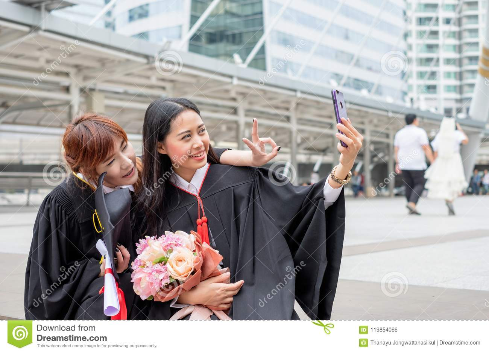 Neemt jong meisje twee een foto met telefoon in viering een graduati