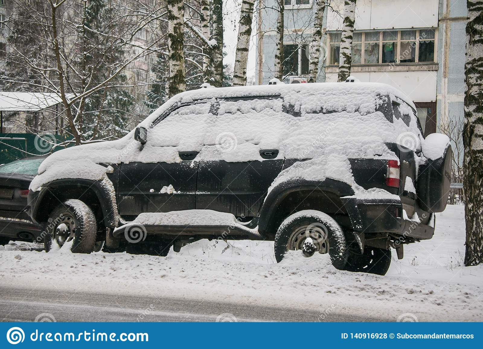 The car, covered with thick layer of snow, in the yard of residential house in provilcial town.
