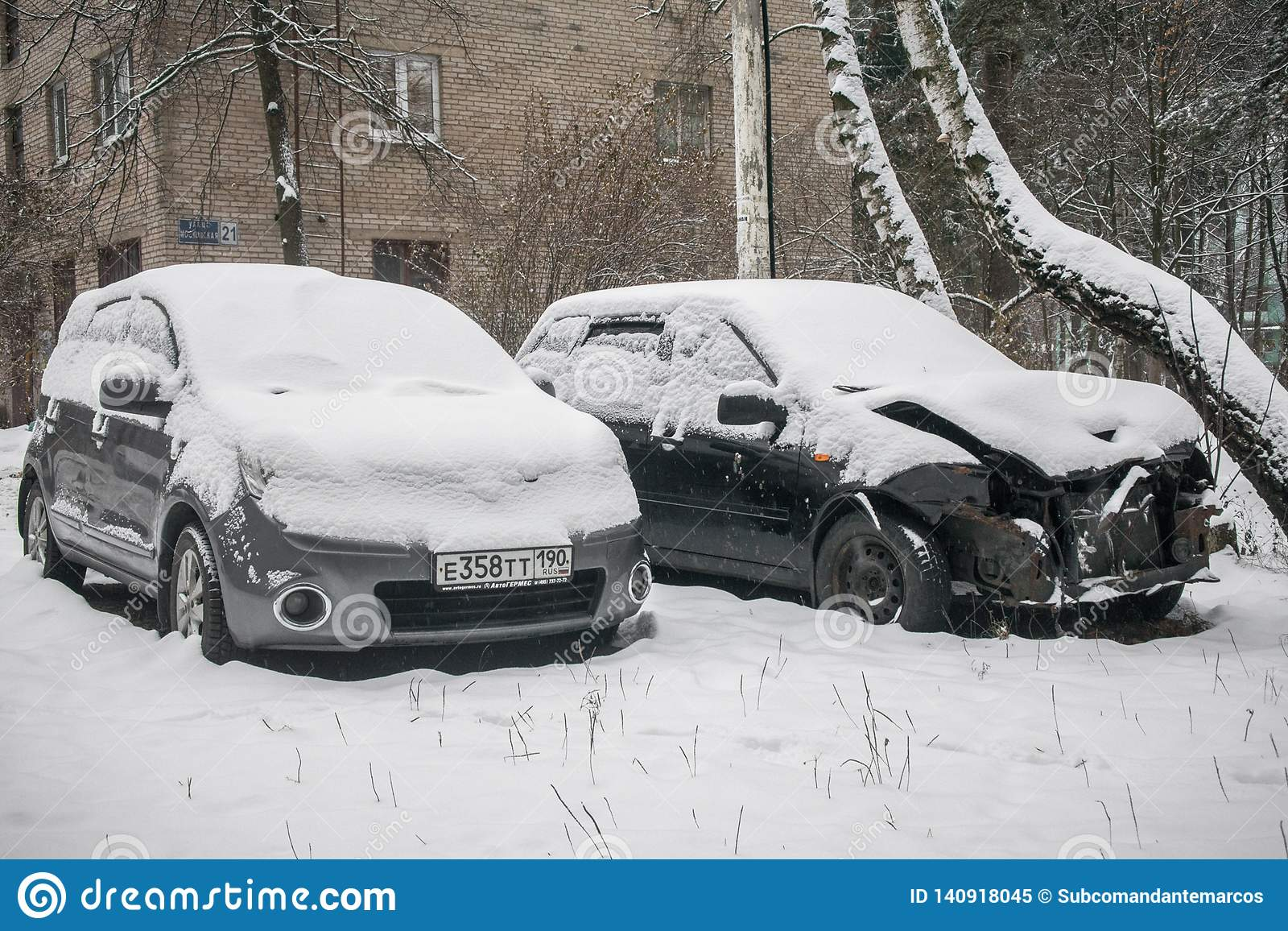 The cars, covered with thick layer of snow, in the yard of residential house in provilcial town.