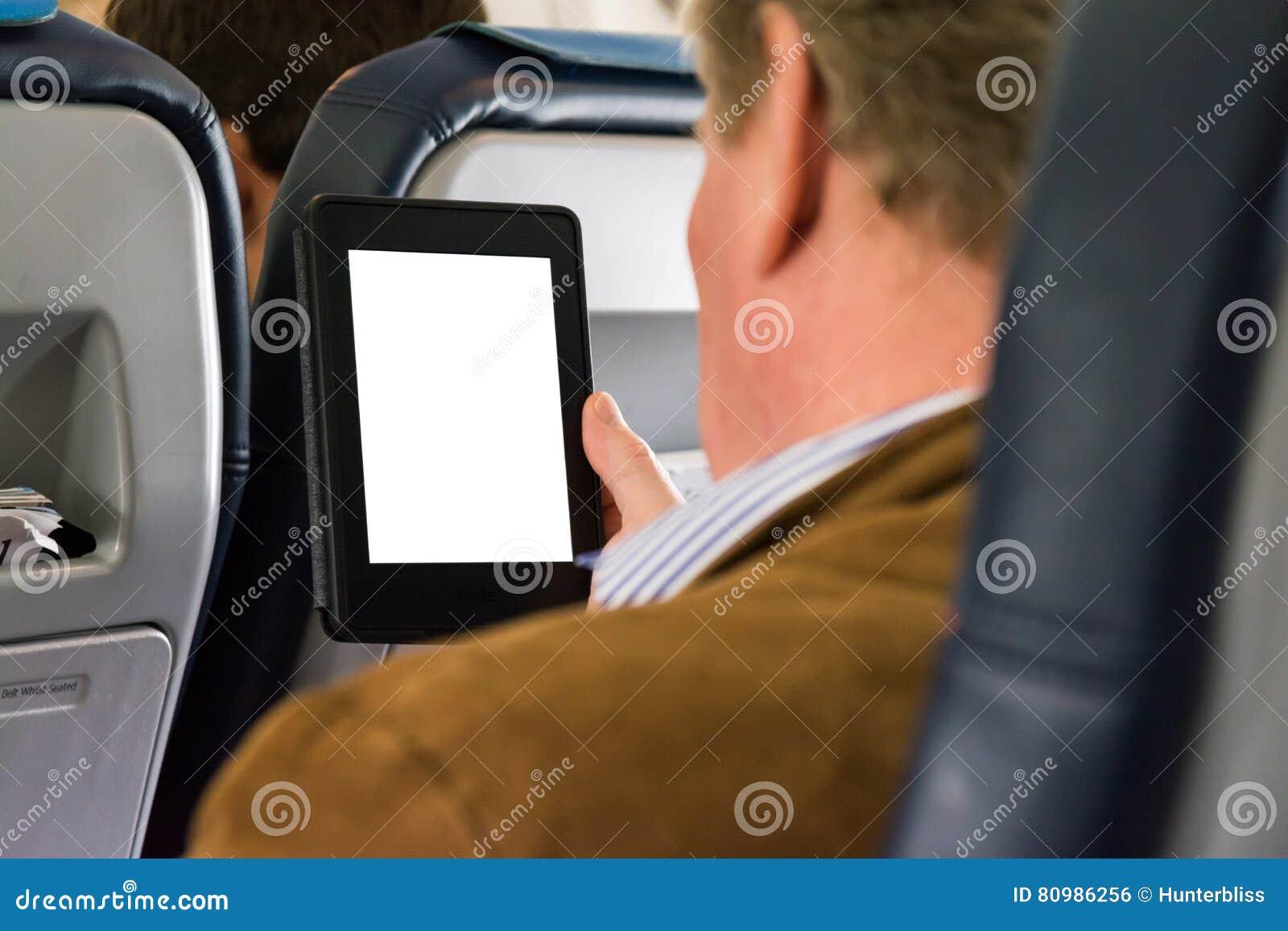 Negocio casual de Seat del aeroplano del hombre que lee la tableta blanca en blanco E-R