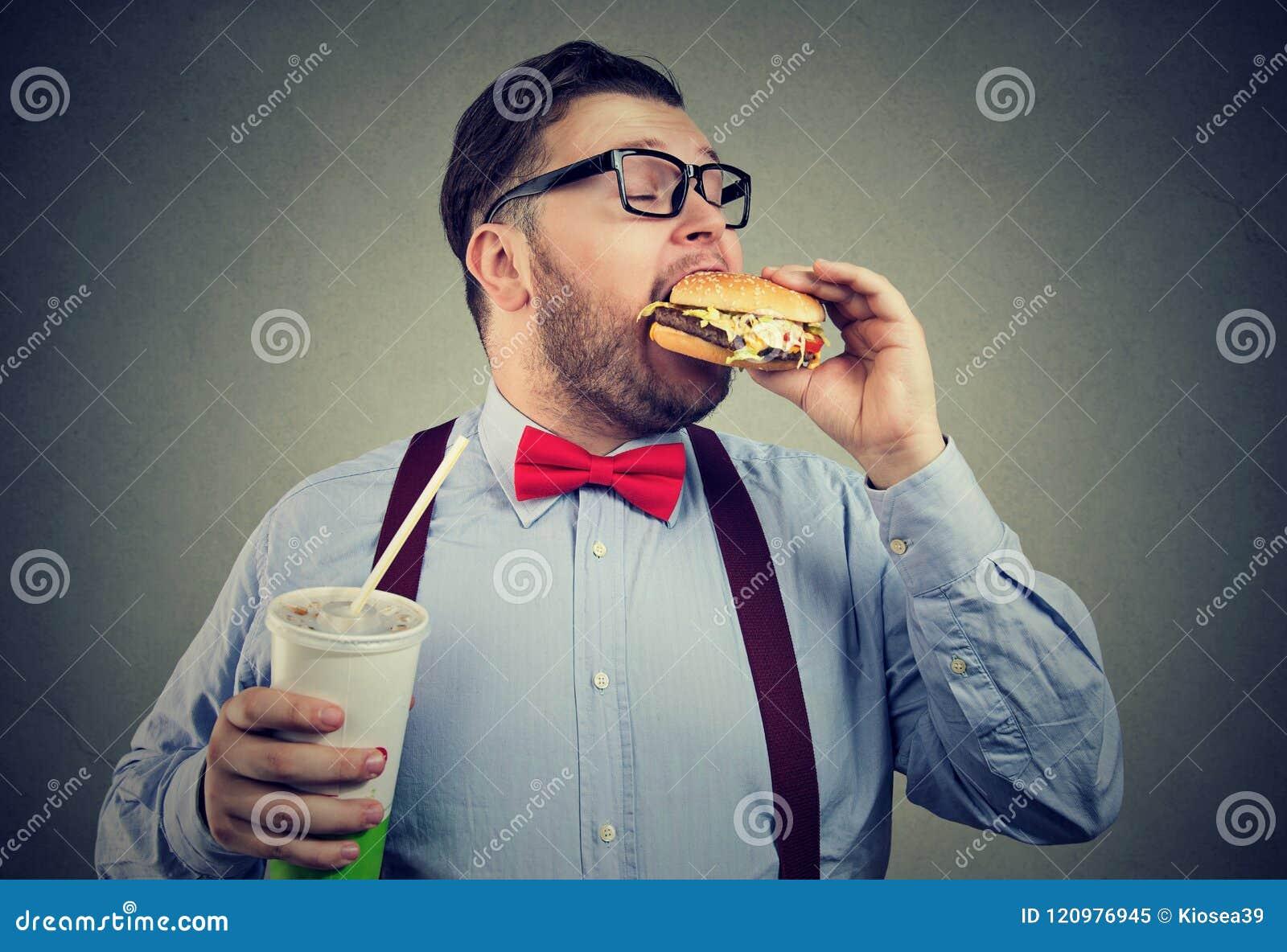 Negocio gordo antropófago con apetito una hamburguesa que sostiene una poder de la bebida de la soda