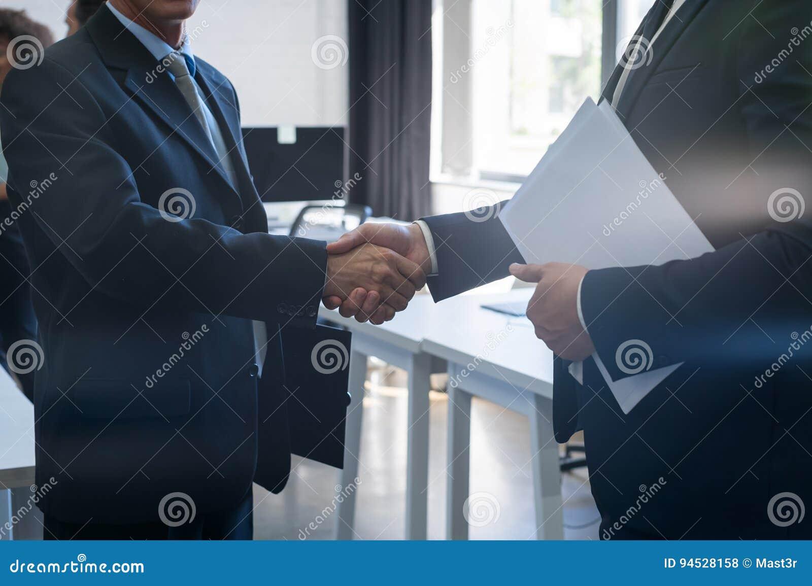 Negocio irreconocible Team Coworkers del centro de Coworking del acuerdo de la mano de la sacudida del hombre de negocios dos