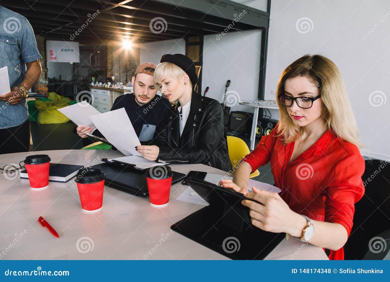 Negocio, tecnolog?a y concepto de la gente - equipo creativo con los ordenadores de la PC de la tableta en la oficina