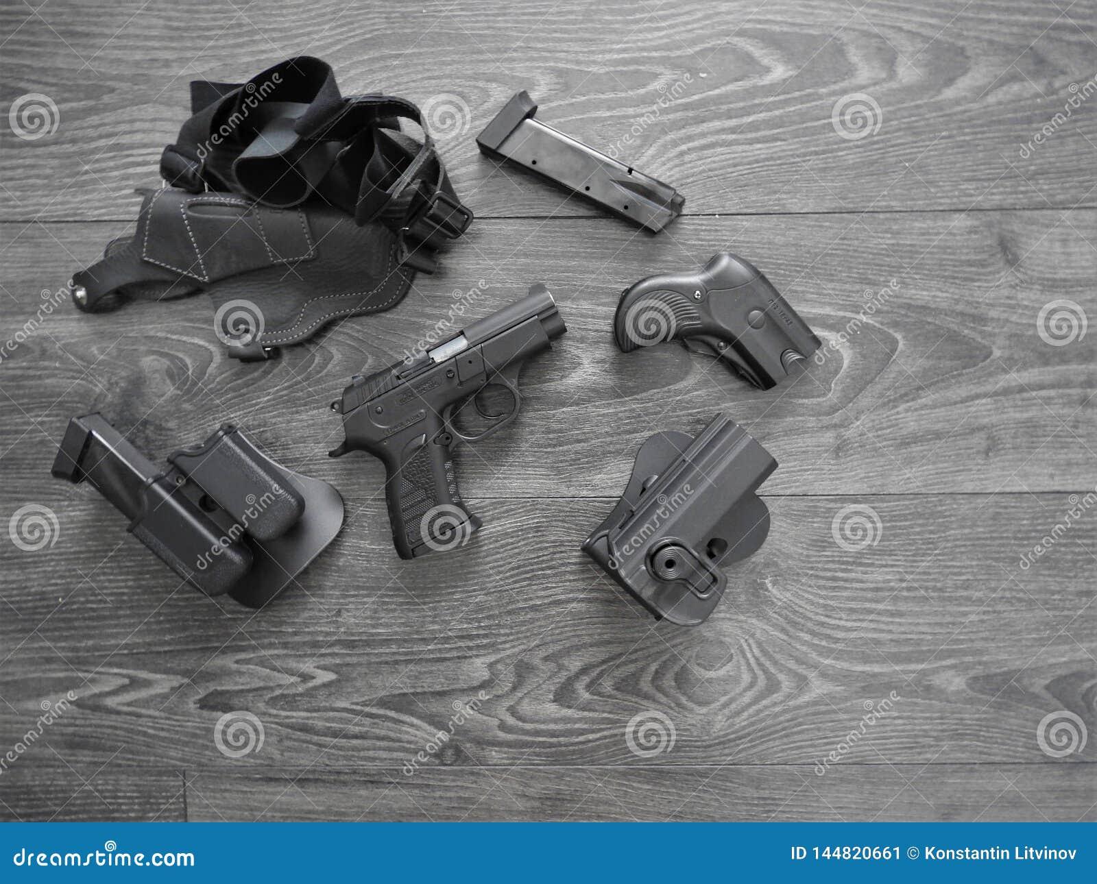 Negro del arma, revistas de repuesto y pistolera de cuero en fondo gris