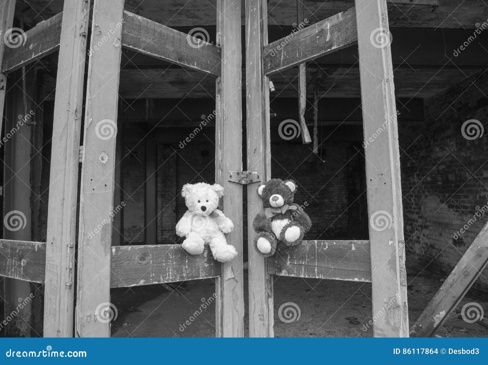 Negro y blanco de Teddy Bears Sitting On Derelict Fie Station Bay Doors In