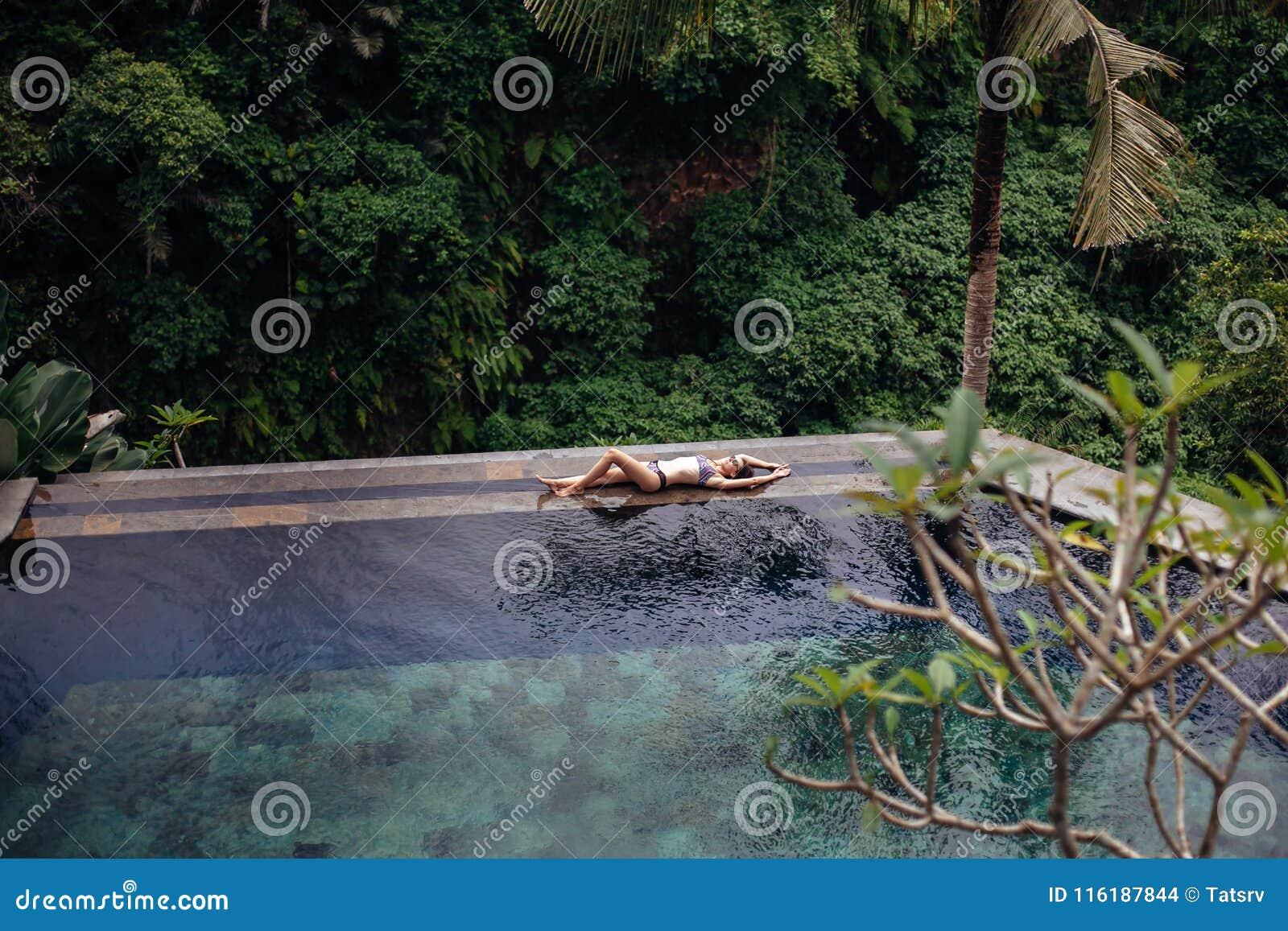 Nehmen Sie sexy Brunettefrau im Badeanzug ab, der auf tropischem Unendlichkeitspool des Randes im Dschungel sich entspannt Palmen