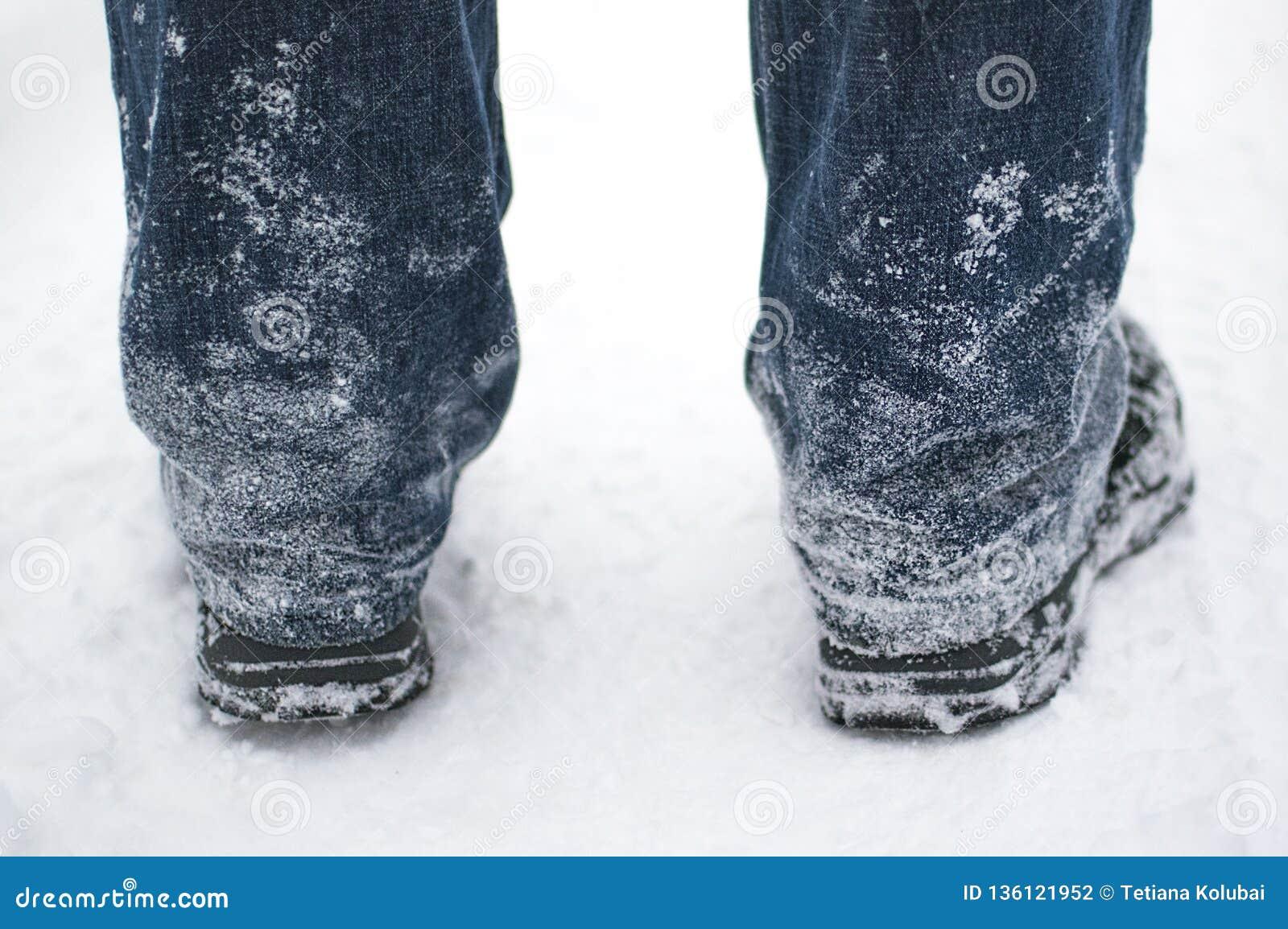 Neige congelée sur des jeans et des bottes noires d un homme en hiver, vue arrière