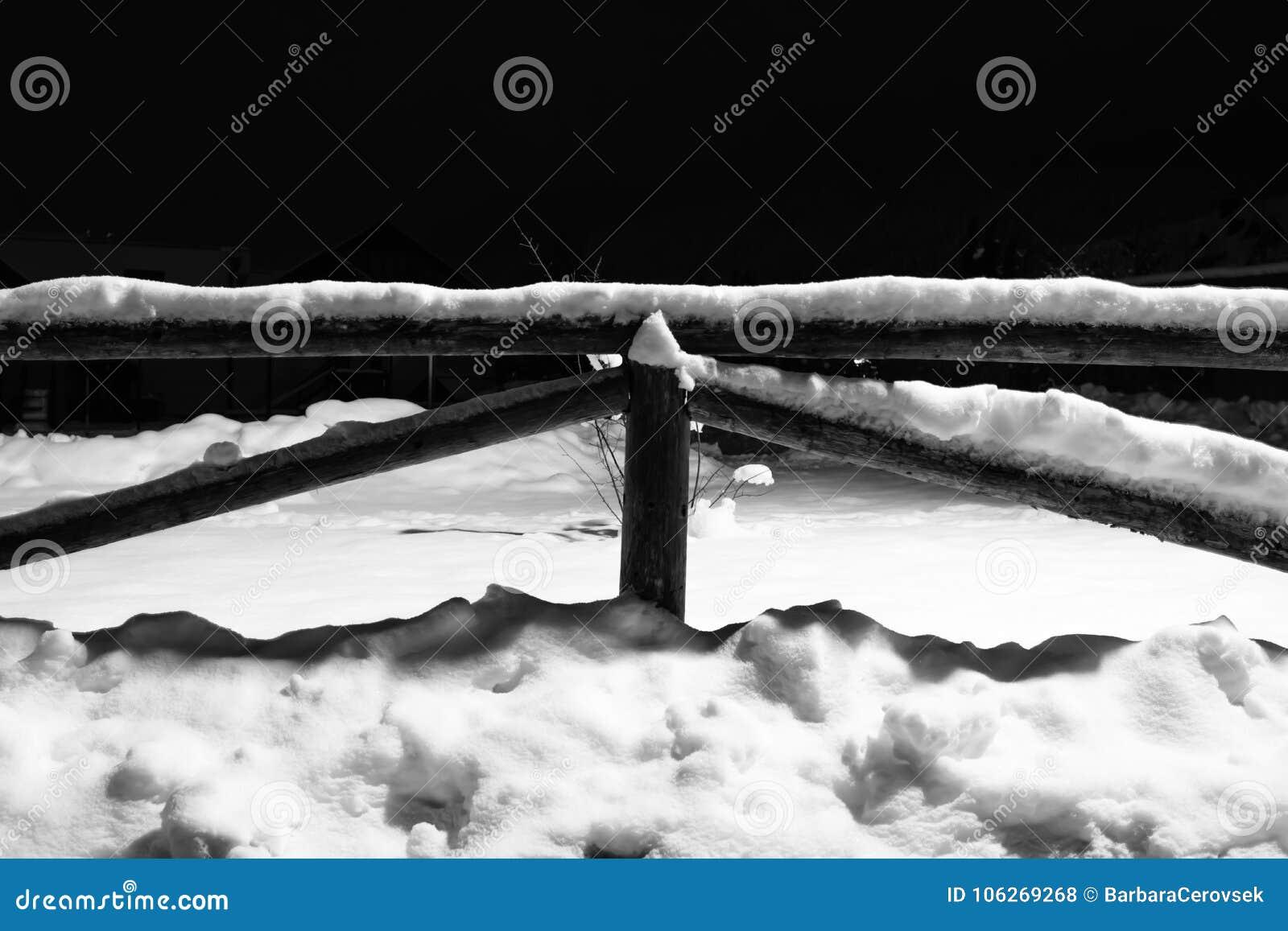 Neige tombée par hiver sur le motif en bois de barrière la nuit